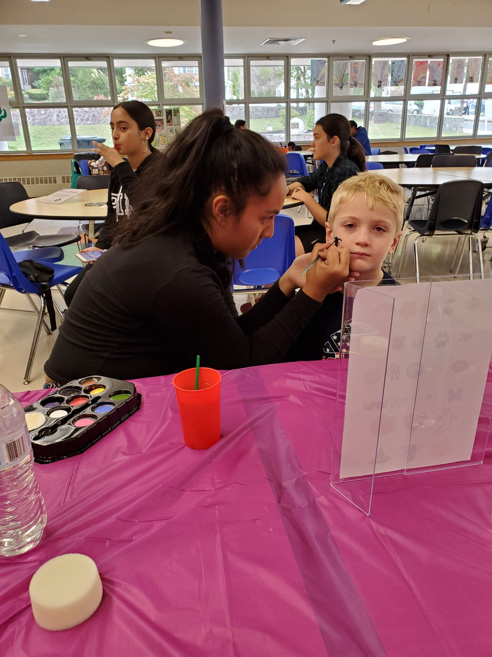 Teen Doing Face Paint for Kids at Public Safety Day Event